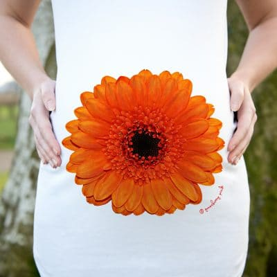 Model wearing white organic maternity top with orange gerbera design by Gooseberry Pink