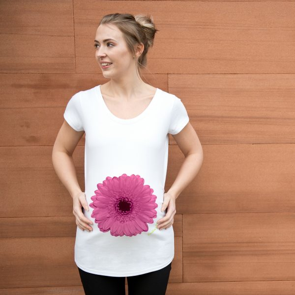 Girl wearing white maternity top with pink gerbera design by Gooseberry Pink