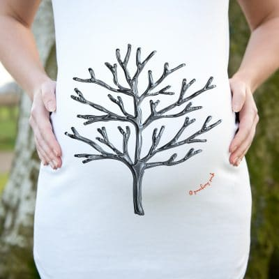 Model wearing white organic maternity top featuring a winter tree design by Gooseberry Pink