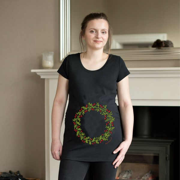 Model wearing black maternity top with holly wreath design by Gooseberry Pink