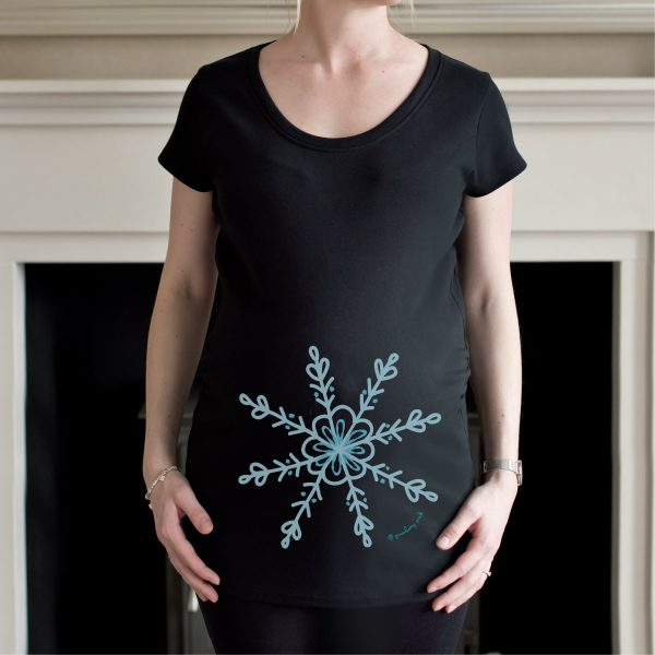 Girl wearing black organic winter pregnancy top with blue snowflake design