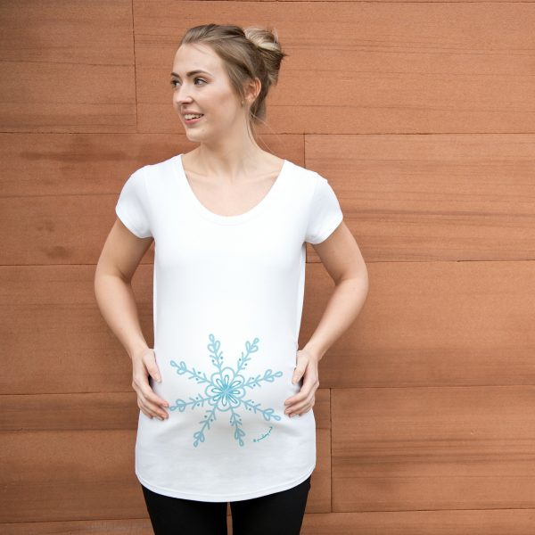 Girl wearing white organic maternity top featuring a blue snowflake design