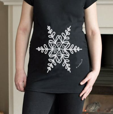 Model wearing a white snowflake maternity top designed by Gooseberry Pink