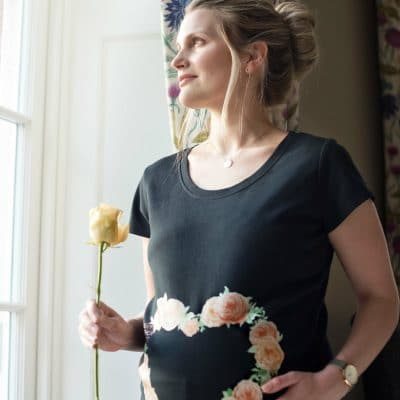 Girl wearing Every Mother Counts orange rose heart logo on black maternity top by Gooseberry Pink