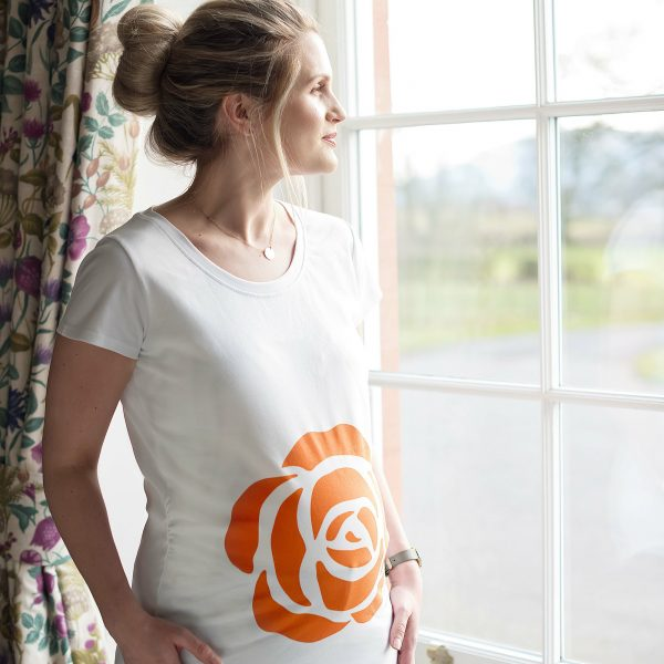 Girl wearing Gooseberry Pink maternity top bearing Every Mother Counts orange rose logo