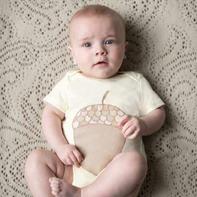 Baby wearing acorn baby bodysuit by Gooseberry Pink