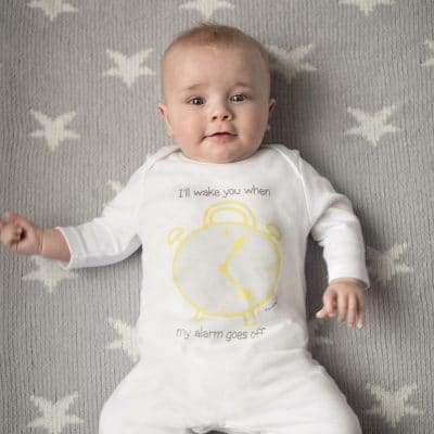 Baby wearing sleepsuit with clock design by Gooseberry Pink