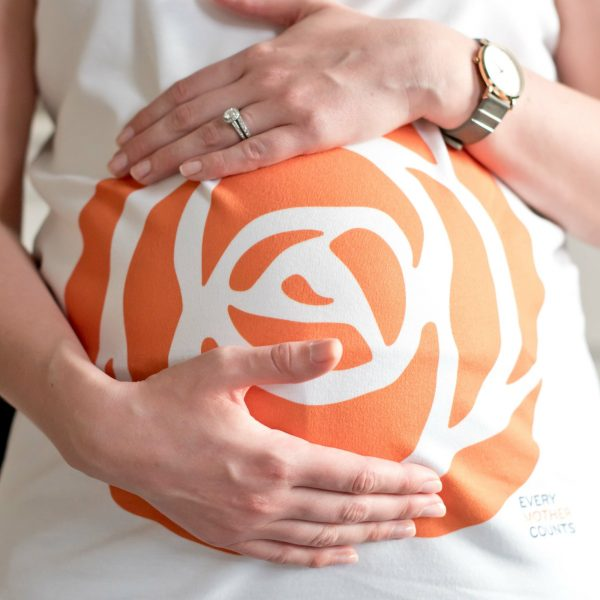 Closeup of Every Mother Counts Orange Rose Logo on White Maternity Top by Gooseberry Pink