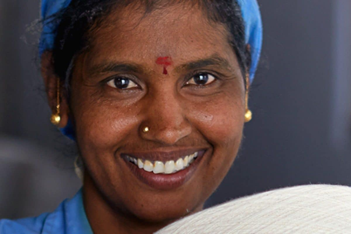textile worker smiling in a kinder world