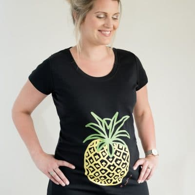 Preganant girl wearing pineapple maternity top on black organic cotton