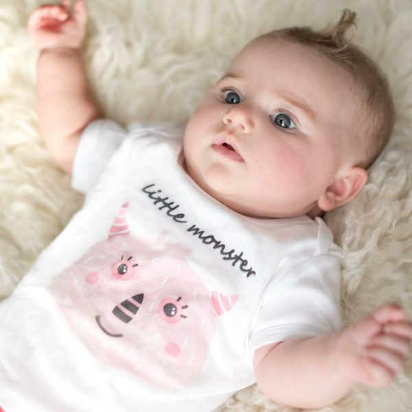 Baby girl wearing white organic baby bodysuit with pink monster design by Gooseberry Pink