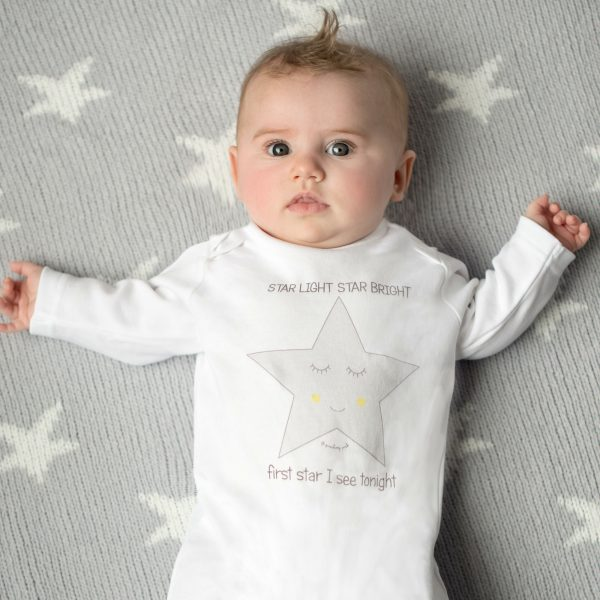 Baby wearing star baby sleepsuit by Gooseberry Pink