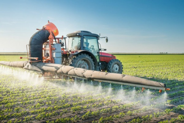 image of tractor spraying cotton plants with pesticide